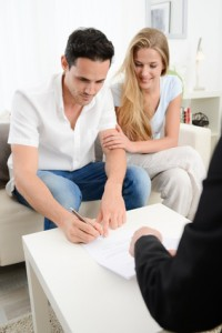 happy young couple at home in transaction signing contract with business woman